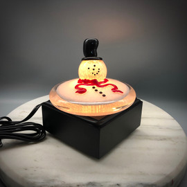 "all Glass Melted version of the Classic glass snowman, featured with black top hat and red scarf. 4"" round. Shown here glowing on a black square illuminating light base."