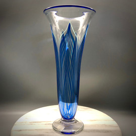 "Blue feather trumpet vase. This gorgeous example is his blue feather combing showcased elegantly over clear glass, with green border accent, This Trumpet style footed vase is about 11.5"" tall and 5"" wide at the top bell.  One of a kind, but can be reproduced upon request if sold."