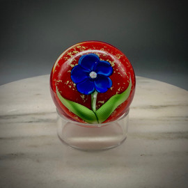 "Chris makes ""one-off"" blossom paperweights, as time and whimsy allow.  This beautiful example showcases a blue five-petal center flower with millefiori center cane, and stylized torchwork leaves hovering over a gorgeous red background, with gold foil accents, encased in Clear glass, hand-shaped, approximately 2 1/2"" tall x 2 7/8"" diameter. ""One-off"" paperweight, featuring contemporary  California-style torchworking techniques, while reminiscent of the antique French paperweights style. One of a kind."