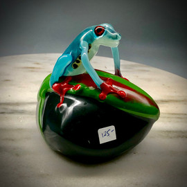 "Another whimsical glass frog creature by Artisan Chris Sherwin at his glassblowing studio.  Costa Rica frog paperweight, Teal blue frog on bright green leaf with red accent on black base, 3"" hand sculpted glass frog with orange murrine eyes, and bright orange feet gripping the base. Made here using several traditional glass sculptural, torchwork and lampworking techniques at Sherwin Art Glass studio overlooking the Connecticut River in Bellows Falls, Vermont."
