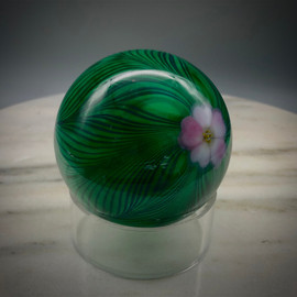 side view of this Cobalt feather weight, over green, with torchwork blush pink 5 petal center flower, 3? paperweight