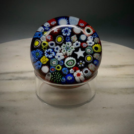 "Chris has had some fun playing with Paperweights when he can, especially utilizing some millefiori cane skills first realized/learned while working with Greg Held at Orient & Flume Art Glass, as well as techniques learned through observing many antique paperweight books, and some new found skills taking master classes at the Corning Museum of Glass. This all glass paperweight features lots of cog, murrine and complex canes. Millefiori closepack over  orange blue swirl background. Lots of time in making, setting, and encasing the canes goes into these glass paperweights. Made by Glass Artisan Chris Sherwin in his Bellows Falls VT glassblowing studio./ 2 3/8"" x 2 3/4"" approx. size. 18/150 lim edition. this edition featues at least one Signature ""S"" cane and ladybug murrine cane."
