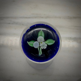 """Nosegay Paperweight, glass paperweight, with torchwork leaves and millefiori cane, over dk cobalt blue background, made by glass artisan Chris Sherwin in his Vermont glassblowing studio. One of a kind. 2"""""""