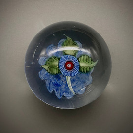 small Nosegay paperweight, glass paperweight, small collectible paperweight, with millefiori and all glass torchwork leaves over blue optic background,  by Chris Sherwin, glassblower in Bellows Falls, Vermont, one of a kind, approx 2""