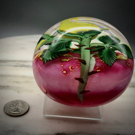 side view of Yellow Rose Paperweight, glass paperweight, torchwork paperweight over pink ruby background by glass artist Chris Sherwin