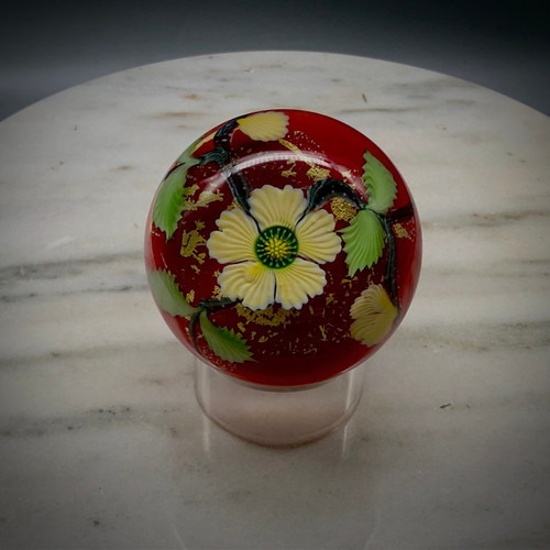 """Chris makes """"one-off"""" blossom paperweights, as time and whimsy allow.  This beautiful example showcases a custard yellow five-petal center flower with millefiori center cane, leaves and bud hovering over a red background accented with gold foil, encased in Clear glass, hand-shaped, approximately 2 1/2"""" tall x 2 3/4-3"""" diameter. """"One-off"""" paperweight."""