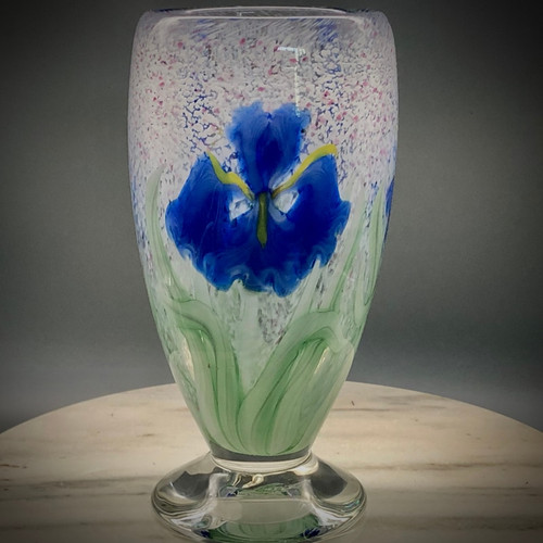 """Blue Iris vase, over """"Gusts of Spring"""" signature background. This gorgeous example features 3 deep veined blue Bearded Iris flowers, each with 4 stylized leaves and yellow accents, using the California style all glass torchworking techniques he learned while working at Orient & Flume Art Glass in Chico, CA--it is a technique best described as """"Painting with glass"""". This elegant footed vase is about 7.75"""" tall and 4"""" wide at the top.  One of a kind, but can be reproduced upon request if sold. hand-sculpted and free blown glass (no molds here!) by glassblower Chris Sherwin, made in Vermont."""