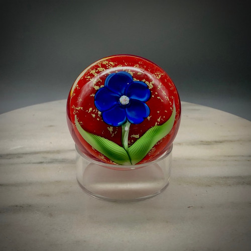 """Chris makes """"one-off"""" blossom paperweights, as time and whimsy allow.  This beautiful example showcases a blue five-petal center flower with millefiori center cane, and stylized torchwork leaves hovering over a gorgeous red background, with gold foil accents, encased in Clear glass, hand-shaped, approximately 2 1/2"""" tall x 2 7/8"""" diameter. """"One-off"""" paperweight, featuring contemporary  California-style torchworking techniques, while reminiscent of the antique French paperweights style. One of a kind."""