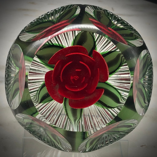 Gorgeous one of a kind Brilliant Red Crimp Rose paperweight, with heart shape center bud, green/black variegated leaves coming to point, made by glass artisan Chris Sherwin in his glassblowing studio in Bellows Falls, Vermont; this weight showcases a 6/1 facet and Picket fence cutting by James Poore of Cape Cod, MA