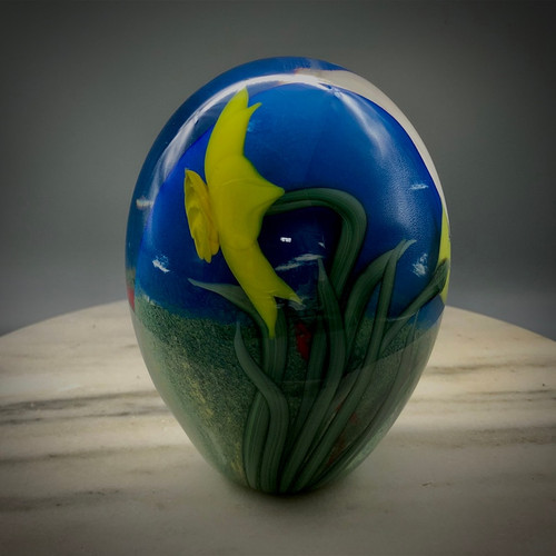 """Daffodil Freeform on signature """"ides of March"""" background, featuring torchwork flowers and slender green leaves, a premade clear bell center and pastel blue background, made by Glass Artisan Chris Sherwin"""