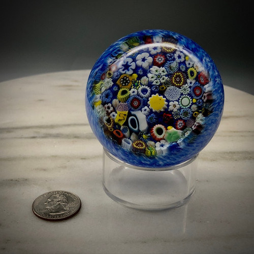 """Chris has had some fun playing with Paperweights when he can, especially utilizing some millefiori cane skills first realized/learned while working with Greg Held at Orient & Flume Art Glass, as well as techniques learned through observing many antique paperweight books, and some new found skills taking master classes at the Corning Museum of Glass. This all glass paperweight features lots of cog, murrine and complex canes. Millefiori closepack over blue speckle muslin background. Lots of time in making, setting, and encasing the canes goes into these glass paperweights. Made by Glass Artisan Chris Sherwin in his Bellows Falls VT glassblowing studio./ 2 3/8"""" x 2 3/4"""" approx. size. this edition featues at least one Signature """"S"""" cane and ladybug murrine cane."""