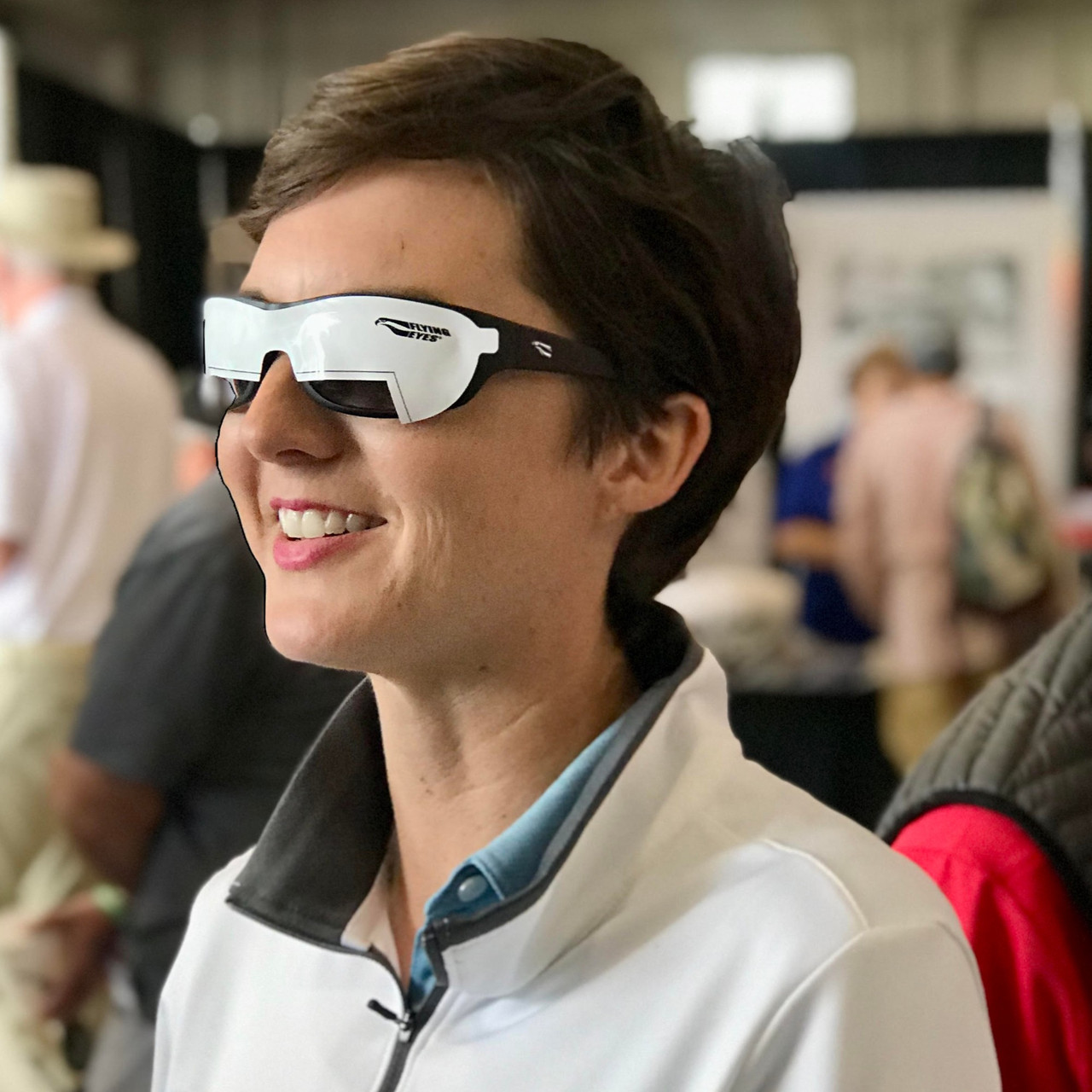 Smiling person wears static cling view limiters for instrument training on their sunglasses.