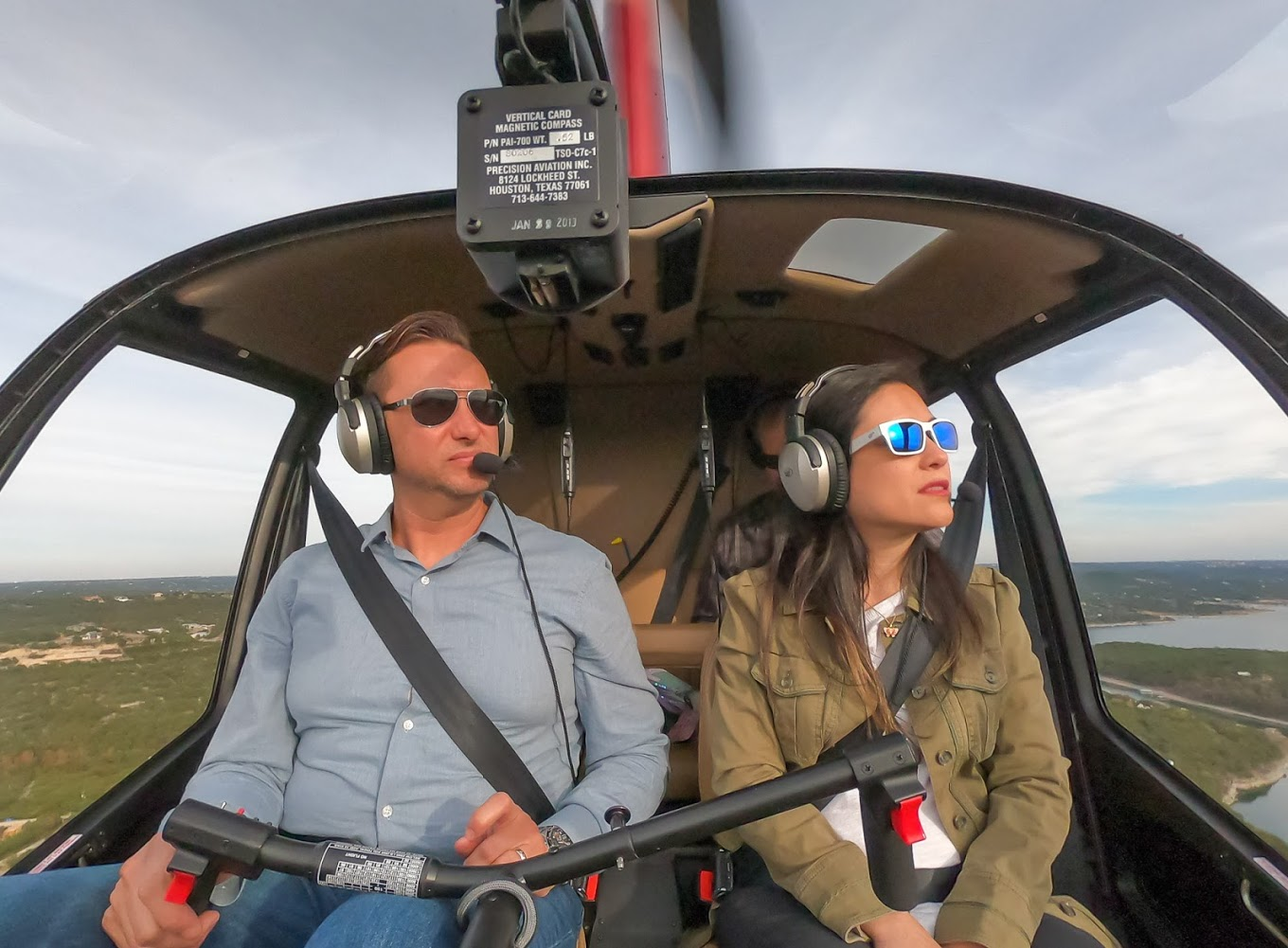 Two helicopters pilots wearing sunglasses and headsets looking out the windows