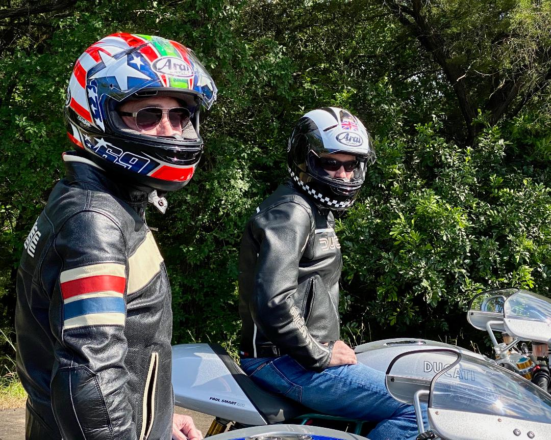 Two motorcyclists wearing sunglasses inside their helmets look at the camera while sitting on their bikes