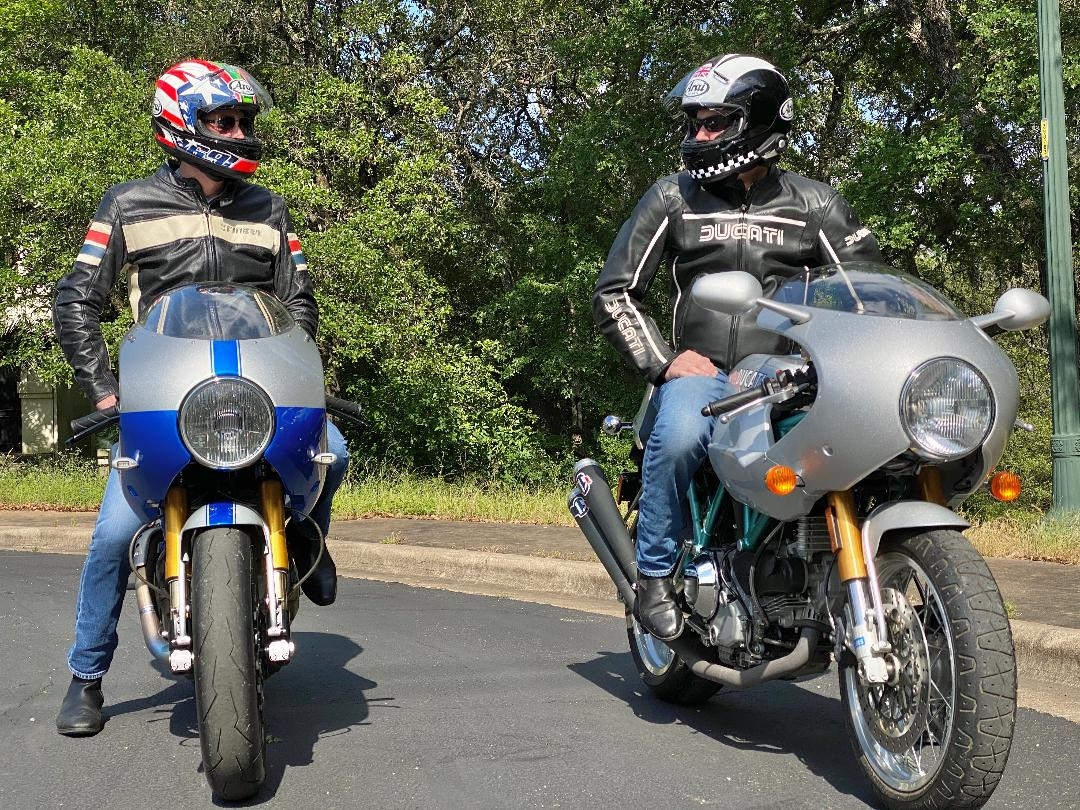 Two motorcyclists wearing sunglasses inside their helmets looking at each other from their bikes.