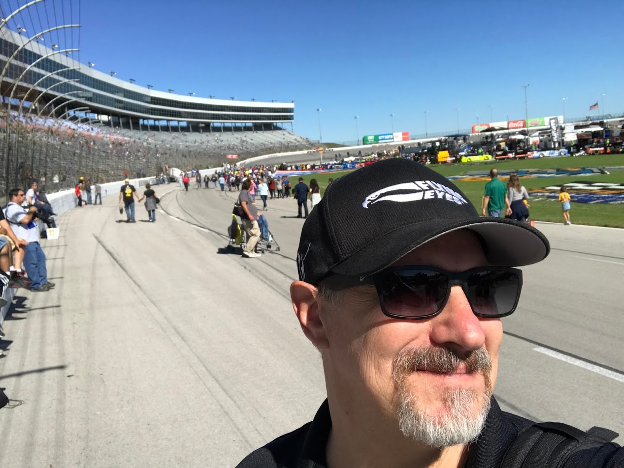 Person wearing a Flying Eyes ball cap and Kingfisher sunglasses stands in front of a race track with people on the track.