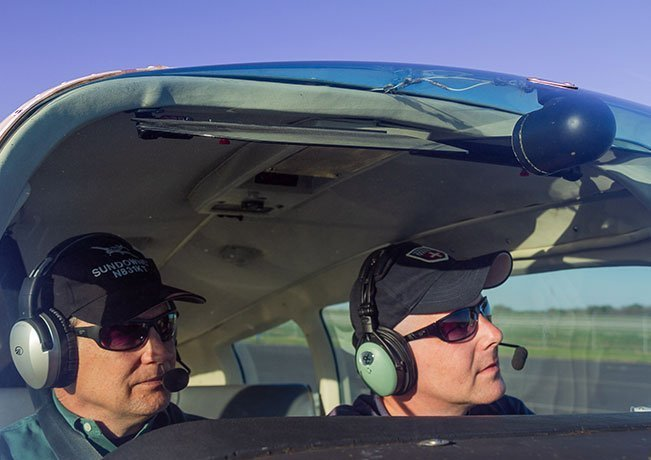 Two pilots wearing sunglasses and ball caps under their headsets look out the windshield of an airplane