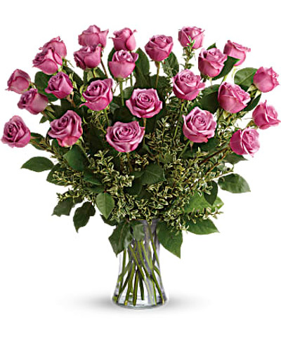 This gorgeous bouquet includes 24 lavender roses, oregonia, and lemon leaf. Delivered in a glass gathering vase. Orientation: All-Around