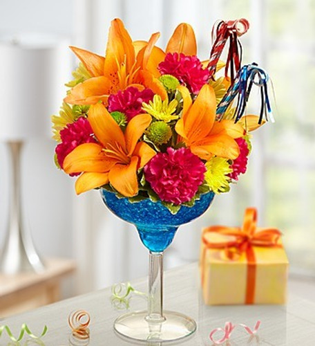 Make every hour of their day Happy Hour with this colorful birthday arrangement in a margarita glass, we hand-arrange the freshest orange lilies, hot pink carnations, green and yellow poms, then add a pair of party horns to get the party started with a smile!