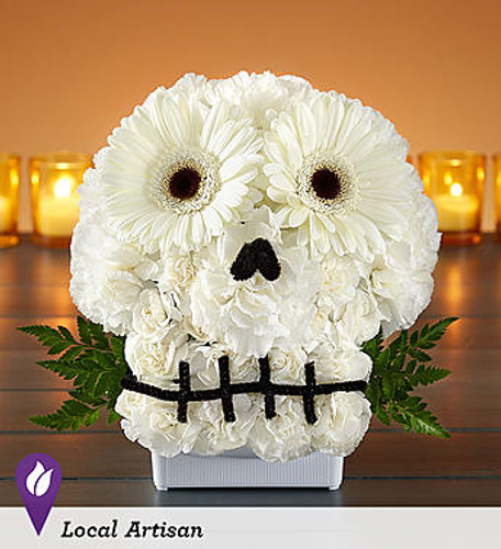 """Spooky Skull Flower Arrangement™ DESIGN COUNCIL EXCLUSIVE Make no bones about it… our truly original skull creation will get everyone into the Halloween spirit. Crafted from all-white blooms, this to-die-for design was made by Sarah Jean from the product development team at 1-800-Flowers.com. """"When I came up with it, I was thinking about my daughter. She basically grew up in a flower shop, and I knew it would bring a smile to her face to see something so different and playful."""" Lighten up the fright by adding a bright, colorful floral tiara for the skull."""