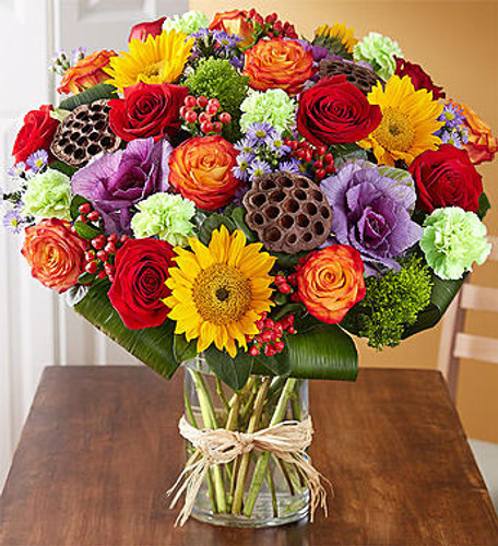 Garden of Grandeur™ for Fall We've taken one of our best-selling bouquets and filled it with all the rich colors and textures of fall. Radiant roses and sunflowers are hand-gathered with a mix of brightly colored blooms and unique accents inside a chic glass cylinder vase. Our vibrant arrangement is sure to delight at every festive gathering.