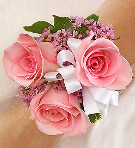 Pink Corsage Light pink roses, pink waxflower and variegated pittosporum laced with white ribbon creates an elegant accompaniment for the mother of the bride or groom, grandmothers, or treasured relatives.