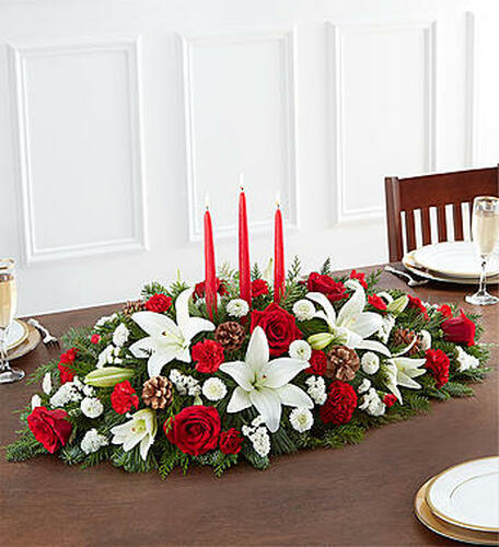 Christmas is a time for celebrating with loved ones, and our traditional holiday table arrangement is at the center of that joy. Beautifully hand-designed with long-lasting blooms in the colors of the season, this fragrant centerpiece features long, red taper candles in the middle to cast a warm, cozy glow for all your guests.