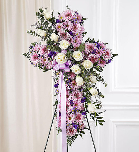 Standing cross arrangement of lavender cremones and daisy poms; white roses; purple limonium, statice and monte casino; accented with soft, lush greenery