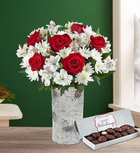 Our traditional best-selling holiday bouquet will deliver your warmest wishes to friends and family this season. Rich, long-stem red roses are paired with clean, white Peruvian lilies and mums to bring festive flair to all your celebrations.