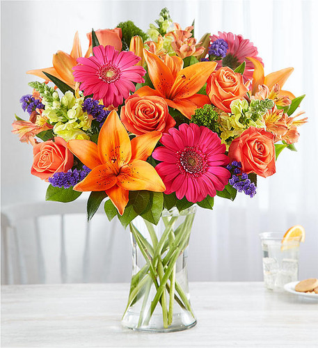 DESIGN COUNCIL EXCLUSIVE Putting a bright start in somebody's day starts with a beautiful gift. Our delightfully vibrant bouquet is filled with a medley of blooms in cheerful pops of orange, pink and yellow, with plenty of lush greenery mixed in.