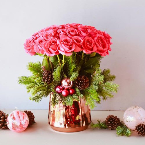 "Embrace the power of pink in this lovely holiday arrangement. Up to 50 magenta pink roses tower up, as Christmas greens, pinecones and pink ornaments rest beneath. Resting inside a 8"" tall rose gold vase, overall this arrangement stands 17"" tall overall."