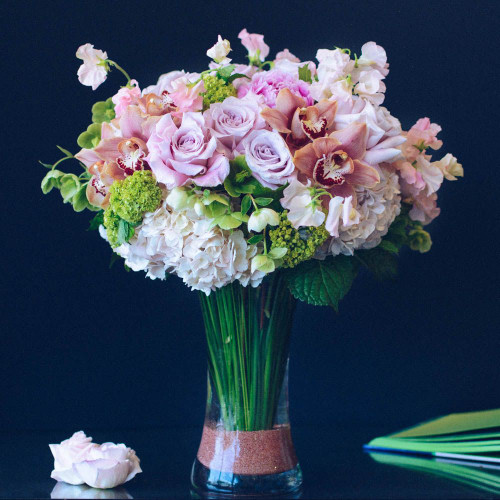 "Lush and whimsical, this blush bouquet is sure to take your breath away. Blush peonies, peach cymbidium blooms, and blush roses rest atop clouds of hydrangea while softly hued sweet peas and bunches of vibernum sprout out from all angles. This stunning design rests within a 12"" tall flared cylinder glass vase complete with metallic rose gold sand, and stands at approximately 20"" tall and 17"" wide overall. **Please note that peonies are currently out of season and a substitute will be used in their place**"