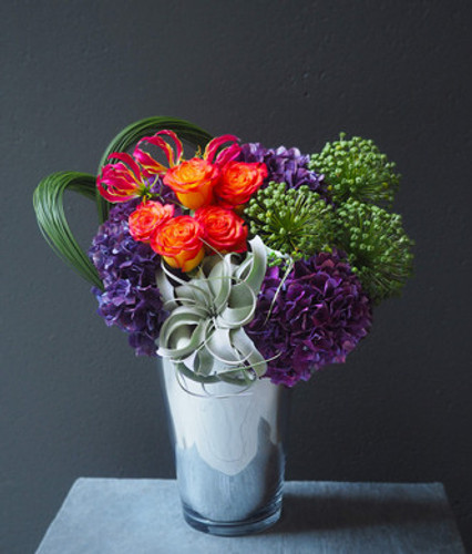 Delight your senses in the rich jewel tones of the season.  This voluptuous arrangement serves a exquisite palette, including decadent Hydrangea, savory Allium, captivating Tillandsia with vibrant Gloriosa Lilies and Roses.