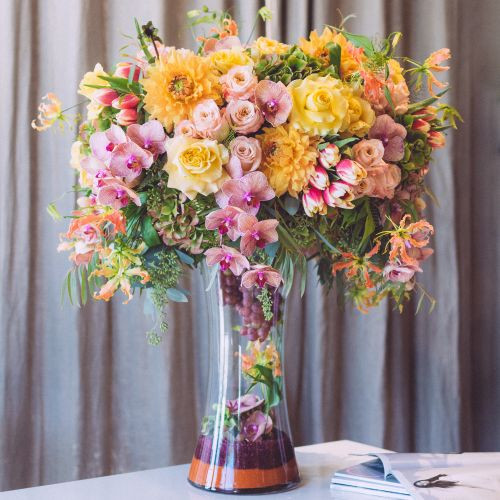 "As stunning as it is grand, this joyous new design is sure to light up any room. Lush tangerine hued dahlias, shimmer roses, yellow turtle roses, and two-toned tulips overflow alongside miniature phalaenopsis stems and whimsical gloriosa lilies. Fresh grapes on the vine and additional blooms can be seen resting within the 20"" tall hour glass vase. Overall, this magnificent arrangement stands at approximately 33"" tall and 26"" wide."