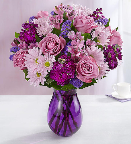 Here's a delightful surprise we've dreamed up just for you. Our expert florists gathered lavender & purple blooms with lush greenery, creating a lovely contrast of color. It's all designed inside our striking violet purple vase to capture its rich beauty, along with the thoughtfulness of your sentiment