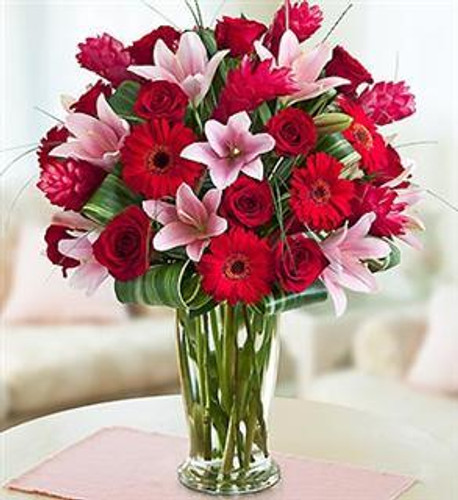 EXCLUSIVE Send a gift that captures the essence of true love with this luxurious bouquet. Our truly original arrangement of vibrant red roses, Gerbera daisies, ginger, lilies, calcynia, bear grass and tropical leaves is stylishly designed in a large chic glass vase to make their day memorable.