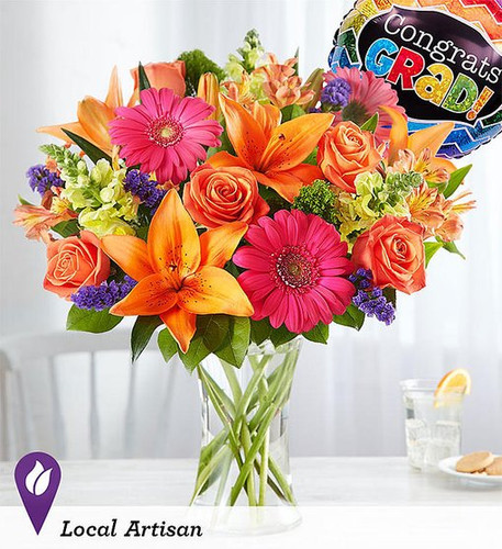 Celebrate a shining star with our best and brightest! Our vibrant graduation bouquet showcases a medley of blooms in cheerful pops of orange, pink and yellow, with plenty of lush greenery mixed in. Designed by Breanna Cartwright from our shop in Modesto, California, it's the perfect surprise to show them how proud you are of their big achievement.