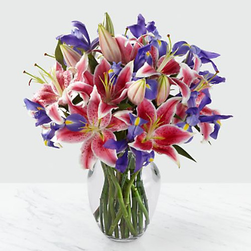 Picked fresh from the farm to make your recipient feel like royalty, our Belle of the Ball Bouquet blooms with a blushing beauty. Hand gathered at select floral farms and bringing together the rich color combination of fuchsia, white, and blue, this exquisite flower bouquet has been picked fresh for you to shower with love and appreciation. Bouquet includes: Stargazer Lilies and light blue iris stems. Presented with a glass vase.