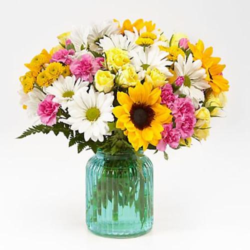 With its sunny hues and fun floral variety, this bouquet will light up the face of whoever you give it to. Through a bright combination of sunflowers, daisy pompons, and spray roses set in a ribbed aqua glass vase, our FTD florists have designed a bouquet that brighten up every moment.