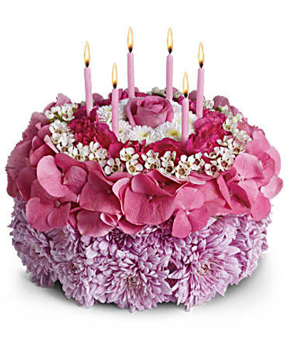 "Pleasing lavender cushion mums, pink hydrangea, white waxflower and button mums are sculpted into a round ""cake"" that's topped with six birthday candles. Orientation: All-Around"