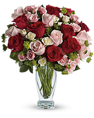 The lush bouquet includes red roses, pink roses, white spray roses and light pink spray roses accented with assorted greenery. Delivered in a clear glass couture vase. Orientation: All-Around