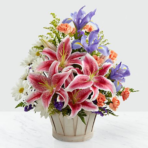 The Wondrous Nature™ Bouquet is bountifully bedecked with a dazzling display of color and beauty. Stargazer lilies stretch their fuchsia petals out amongst an arrangement of blue iris, white traditional daisies, orange mini carnations, purple statice and yellow solidago in a round whitewash handled basket, creating a delightful bouquet your special recipient will adore.