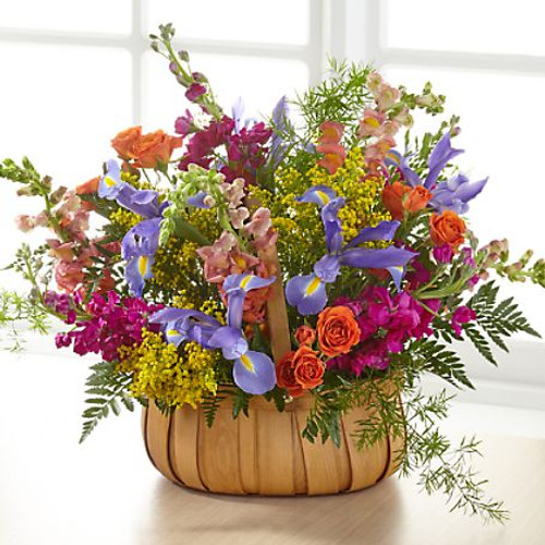 A gorgeous mix of beautiful, bright summer flowers offers an uplifting expression of your sympathy and love. This basket comes designed with iris, stock and roses from a local florist to share your thoughtful sentiments to any service or home.