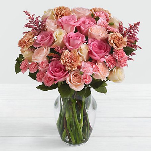 Our Rosy Glow Bouquet is just the pick me up needed to boost their mood and brighten their day. This sweet stunner of a bouquet comes with an incredible array of flowers in peach and pink hues. The blushing shades are accented by a clear vase, to make their color pop! Just a heads up, the blooms will come in bud form, only to open up for long lasting beauty.