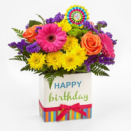 """The Birthday Brights™ Bouquet is a true celebration of color and life to surprise and delight your special recipient on their big day! Hot pink gerbera daisies and orange roses take center stage surrounded by purple statice, yellow cushion poms, green button poms, and lush greens to create party perfect birthday display. Presented in a modern rectangular ceramic vase with colorful striping at the bottom, """"Happy Birthday"""" lettering at the top, and a bright pink bow at the center, this unforgettable fresh flower arrangement is then accented with a striped happy birthday pick to create a fun and festive gift."""