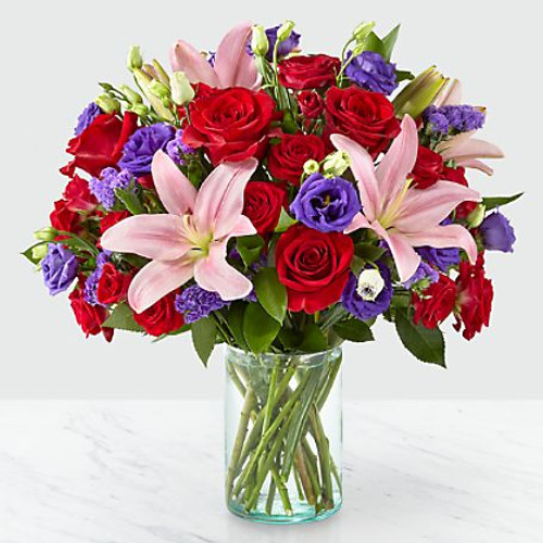 Share a smile with your loved ones through a bouquet filled with stunning beauty and heartfelt joy. Comprised of vivid red roses, purple double lisianthus, pink lilies and red spray roses within a clear glass vase, vibrant color bursts from every bloom. Make their day brighter with a gift that is Truly Stunning™!