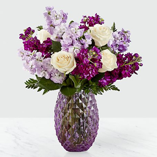 Let those know you hold them dear in a truly beautiful way. An array of cream roses and hues of violet stock burst from a lavender glass vase with a diamond pattern and comes together to create an artful collection of flowers. Whether it's a long-distance friend or a family member down the street, this collection of flowers makes for a sweet gift.