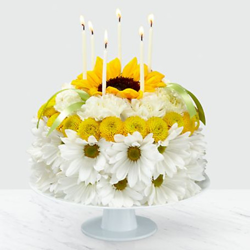 Blow out the candles, and help make it their brightest birthday yet with our Birthday Smiles Floral Cake. This one-of-a-kind arrangement is frosted with a collection of bright sunflowers, yellow button pompons, white daisy pompons and white carnations. Topped with birthday candles and satin ribbon, this unique gift will bring a smile to their face and make it a truly memorable celebration.