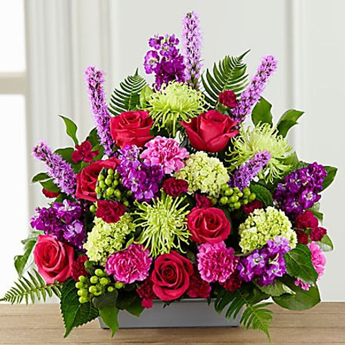 "A lovely way to say, ""farewell,"" this bright, beautiful arrangement expresses your sympathy with color, texture and floral artistry, while comforting grieving friends and family. This handcrafted bouquet is handcrafted by a local FTD florist and makes a vibrant statement with hot pink roses, pink and fuchsia carnations, purple stock, green spider chrysanthemums, mini-hydrangea and hypericum berries all accented with sword fern and salal in a low rectangle container of silvery metallic plastic."