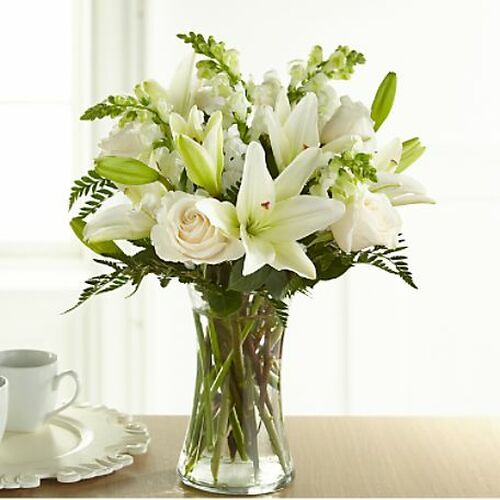 "An exuberance of bright and beautiful white blossoms provides an exquisite way to deliver your expressions of sympathy and comfort. This life affirming tribute combines white roses, snapdragons and Asiatic lilies accented by lush greens arranged in a clear glass 8"" vase. An excellent choice for a wake, funeral service or for sending your condolences to the home of grieving family or friends."